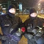 Polizisten mit Rosen nach der Demo