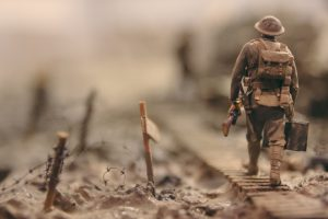 soldier walking on wooden pathway surrounded with barbwire selective focus photography © Photo by Stijn Swinnen on Unsplash